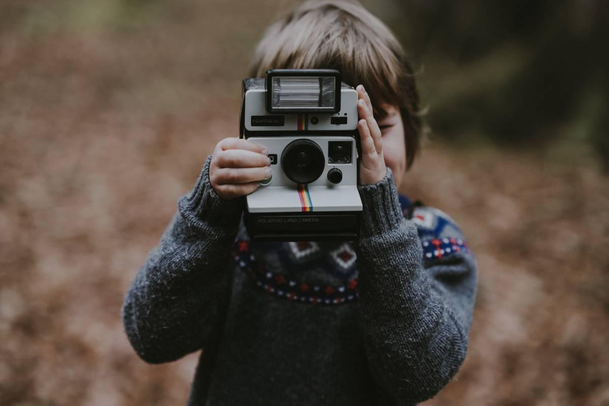 Enfant avec appareil photo polaroid