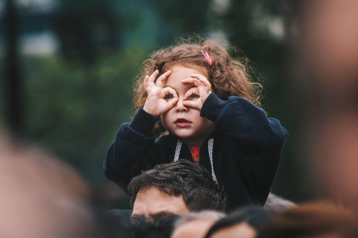 Petite fille faisant des lunettes avec ses doigts