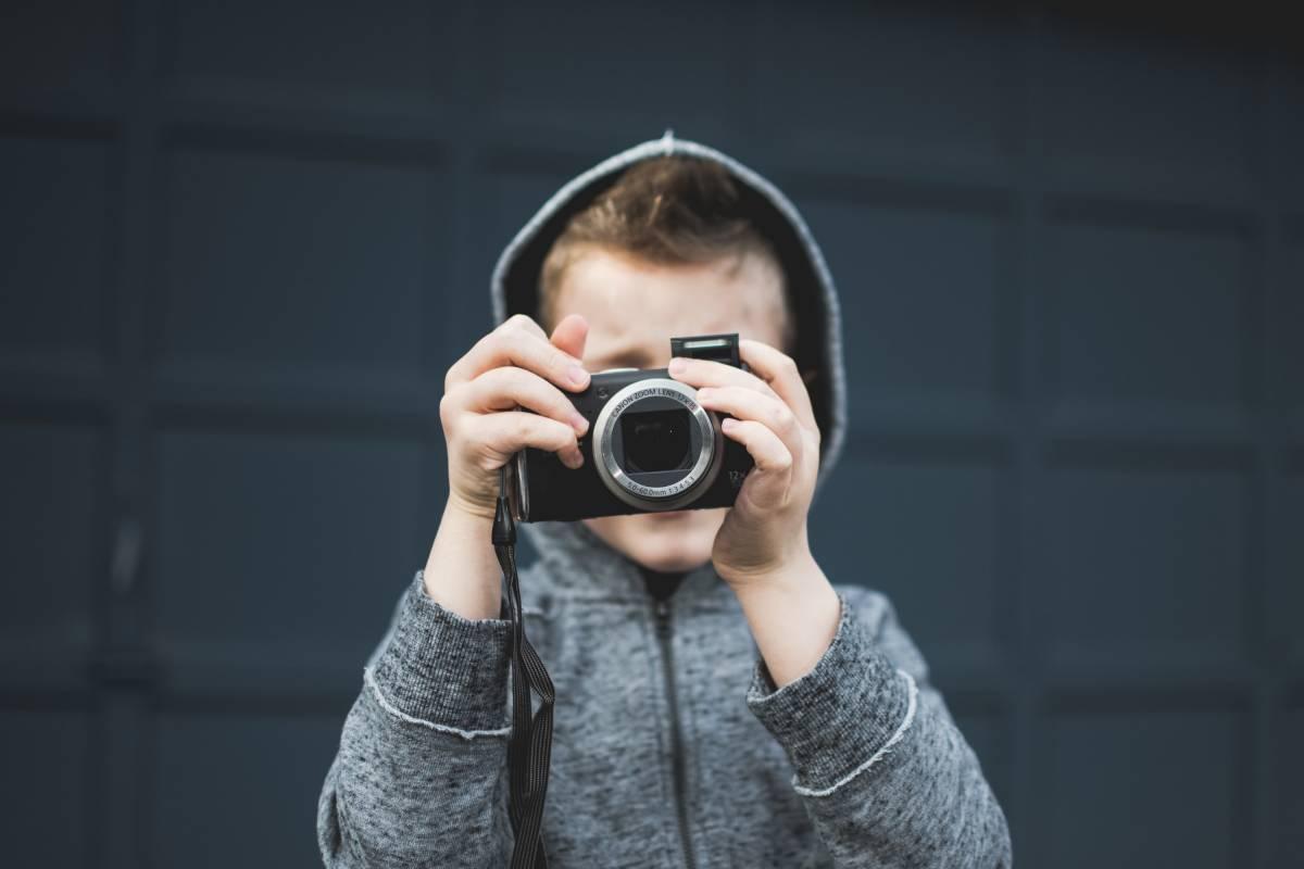 Enfant avec un appareil photo devant son visage