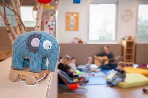Dans une crèche un animateur musical joue de la guitare entouré d'enfants