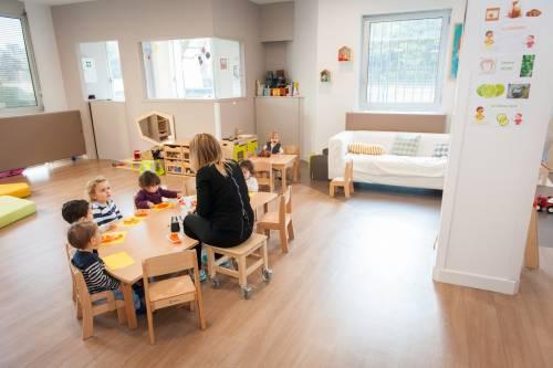 Une éducatrice de jeunes enfants discute avec des enfants dans une crèche