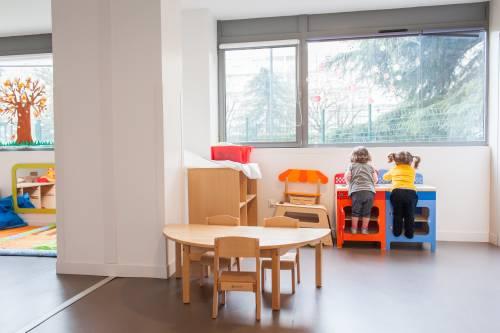 Dans une crèche, 2 enfants regardent par la fenêtre
