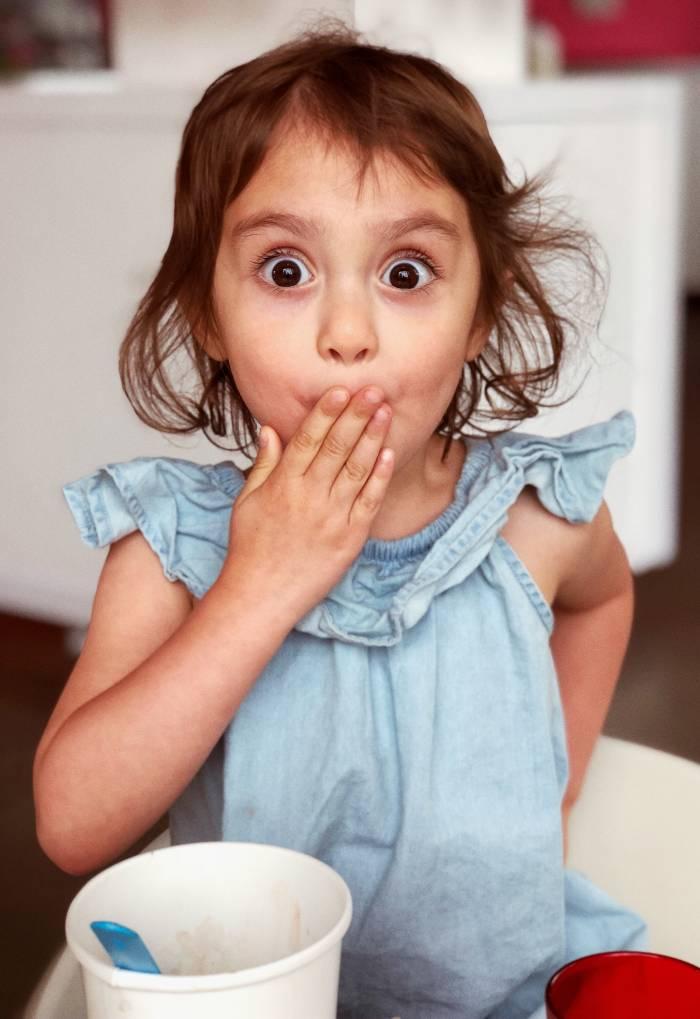 Petite fille avec la main devant la bouche